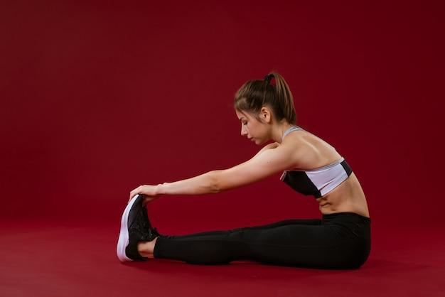 Młoda kaukaska kobieta w stroju sportowym robi rozciąganie na czerwonym tle sportowego stylu życia i ciała c...
