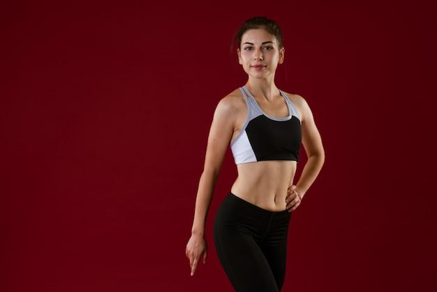 Młoda kaukaska kobieta w stroju sportowym z piękną talią pozuje na czerwonym tle