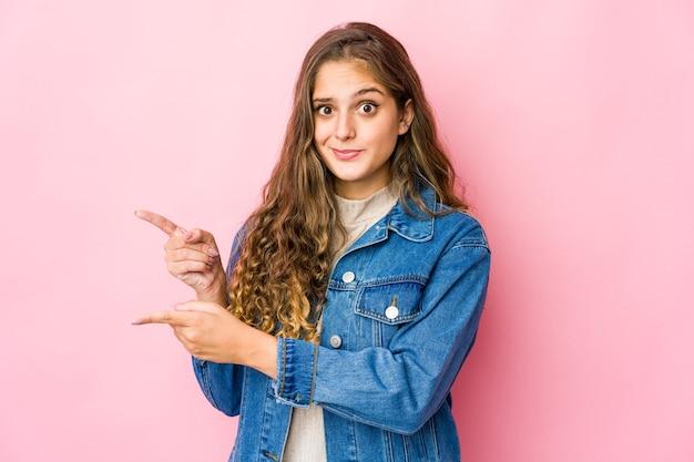 Młoda kaukaska kobieta w szoku wskazując palcami wskazującymi na przestrzeń kopii.