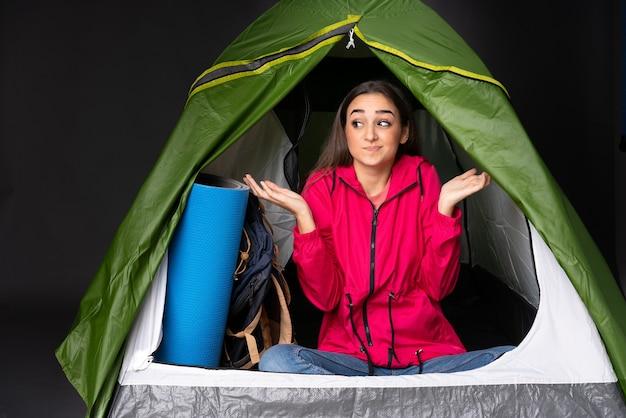 Młoda kaukaska kobieta w zielonym namiocie kempingowym ma wątpliwości podczas podnoszenia rąk
