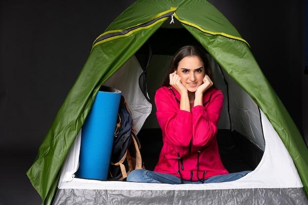 Młoda kaukaska kobieta w zielonym namiocie kempingowym sfrustrowana i zakrywająca uszy