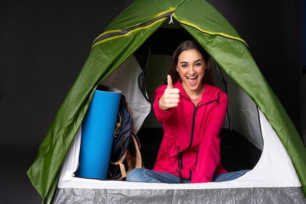 Młoda kaukaska kobieta w zielonym namiocie kempingowym z kciukami do góry, ponieważ wydarzyło się coś dobrego