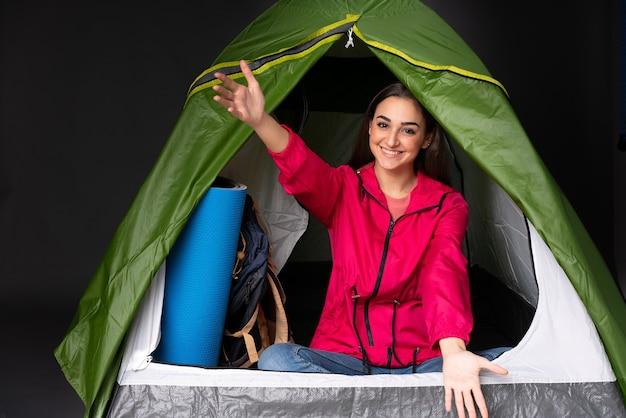 Młoda kaukaska kobieta w zielonym namiocie kempingowym, zapraszając do wejścia