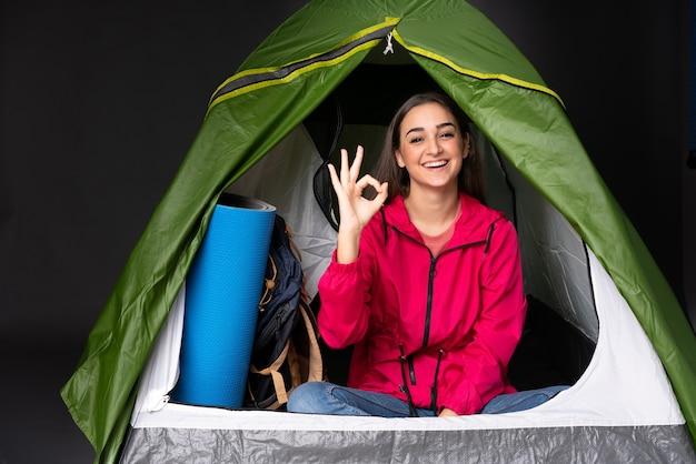 Młoda kaukaska kobieta wewnątrz zielonego namiotu kempingowego pokazuje znak ok palcami