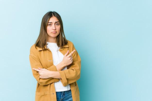 Młoda kaukaska kobieta wskazuje na boki i próbuje wybrać jedną z dwóch opcji.