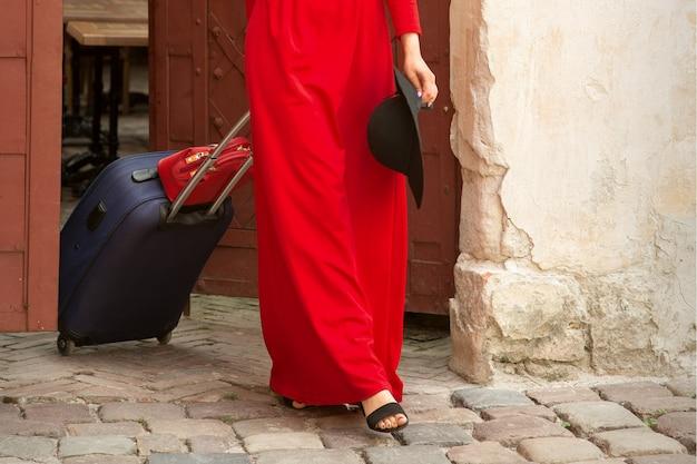 Młoda kaukaska kobieta wychodzi ze starożytnych drzwi z bagażem na ulicy starego miasta