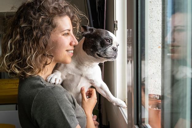 Młoda kaukaska kobieta z buldogiem w domu. poziomy widok kobiety trzymającej psa dziecka w oknie.