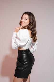 Młoda kaukaska kobieta z falującymi brązowymi włosami, ubrana w białą bluzkę i czarny garnitur, uśmiechnięta na szarym tle