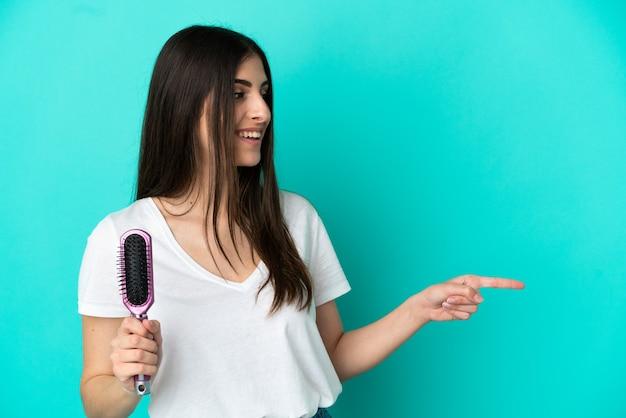 Młoda kaukaska kobieta z grzebieniem do włosów na białym tle na niebieskim tle skierowana w bok, aby zaprezentować produkt