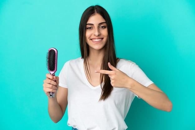Młoda kaukaska kobieta z grzebieniem do włosów odizolowana na niebieskim tle i wskazująca go