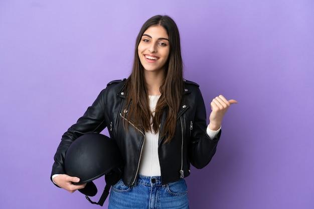 Młoda kaukaska kobieta z kaskiem motocyklowym odizolowana na fioletowym tle skierowana w bok, aby zaprezentować produkt