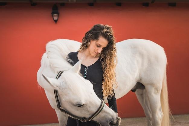 Młoda kaukaska kobieta z koniem w ośrodku jeździeckim