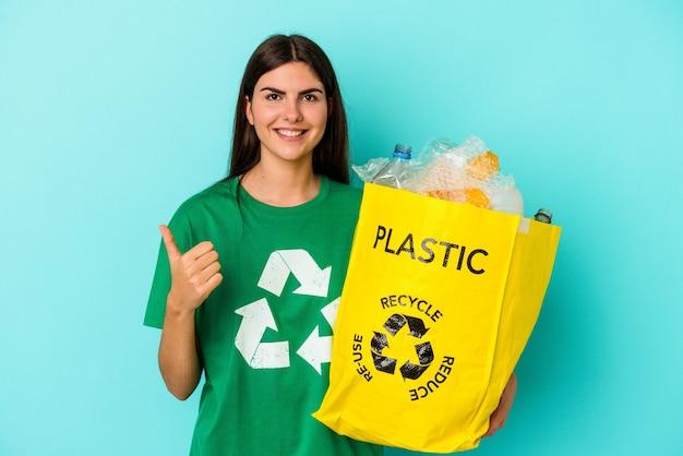 Młoda kaukaska kobieta z recyklingu plastiku na białym tle na niebieskim tle uśmiecha się i podnosi kciuk w górę