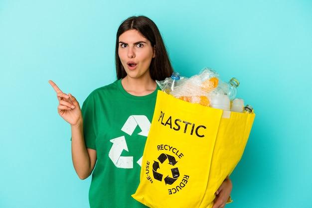 Młoda kaukaska kobieta z recyklingu plastiku na białym tle na niebieskim tle, wskazując na bok