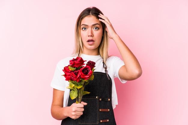 Młoda kaukaska kobieta z różami w szoku, przypomniała sobie ważne spotkanie.