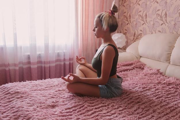 Młoda kaukaska, ładna, uważna kobieta medytuje z zamkniętymi oczami, siedząc na łóżku w sypialni