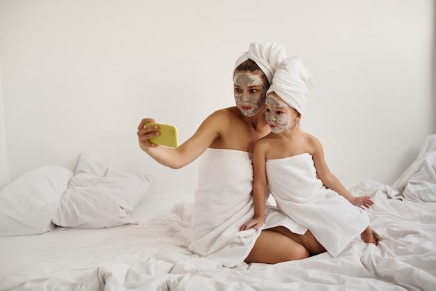 Młoda kaukaska matka i córeczka z owiniętymi włosami w białe ręczniki kąpielowe z maską na twarzach bawią się i robią selfie przez telefon