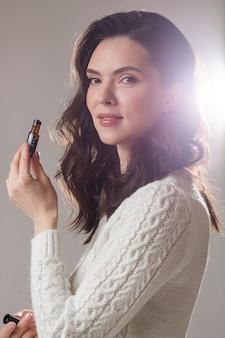 Młoda kaukaska modelka z długimi ciemnymi włosami pozuje do aparatu z ręką blisko twarzy