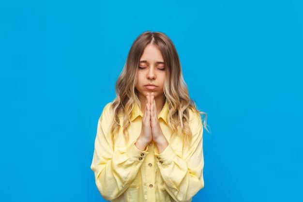 Młoda kaukaska piękna blondynka w żółtej koszuli modli się z zamkniętymi oczami i założonymi rękami dzięki składaniu życzeń prosząc o pomoc, nadzieję lub przebaczenie na jasnym kolorze niebieskiej ściany