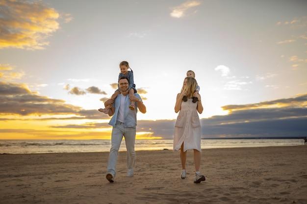 Młoda kaukaska piękna para z dziećmi na ramionach o zachodzie słońca na plaży latem