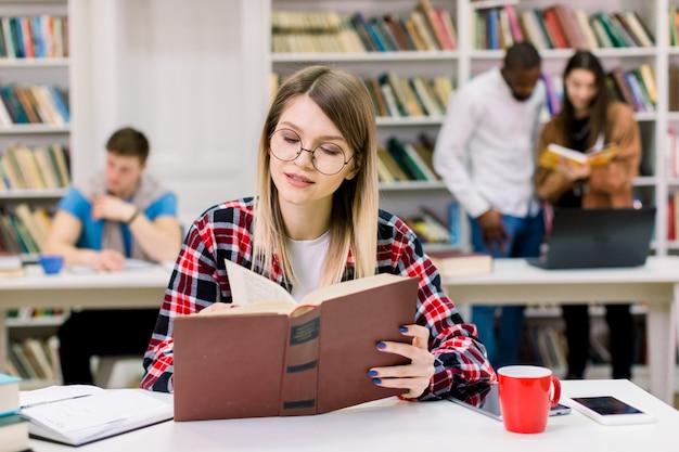 Młoda kaukaska piękna studencka dziewczyna studiuje w szkłach, czyta potrzebną informację z książki podczas gdy siedzący przy stołem w nowożytnej bibliotece uniwersyteckiej. mieszane rasy studentów w kosmosie