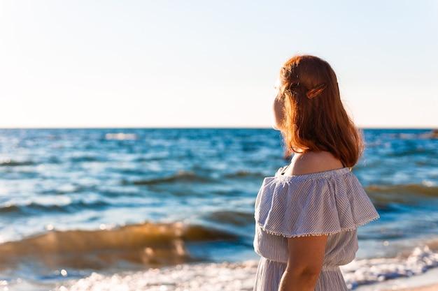 Młoda kaukaska rudowłosa dziewczyna z plecami stoi na plaży w pobliżu morza i patrzy na świt