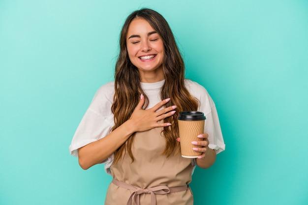 Młoda kaukaska sprzedawczyni w sklepie trzymająca kawę na wynos na białym tle na niebieskim tle śmieje się głośno trzymając rękę na klatce piersiowej.