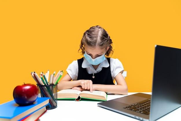 Młoda kaukaska uczennica siedzi przy biurku i czyta książkę w masce z nauką na odległość z laptopa