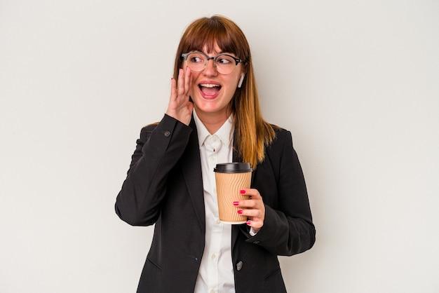 Młoda kaukaski biznes krzywego kobieta trzyma kawę na białym tle krzycząc i trzymając dłoń w pobliżu otwartych ust.