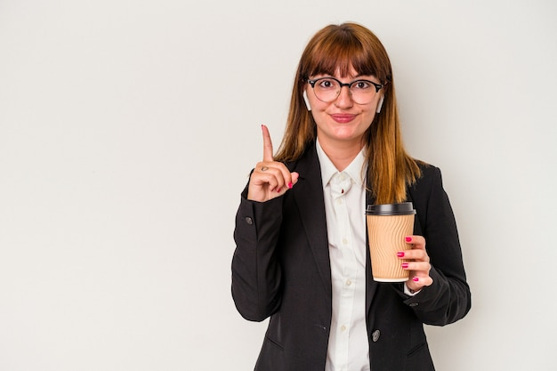 Młoda kaukaski biznes krzywego kobieta trzyma kawę na białym tle pokazując numer jeden z palcem.