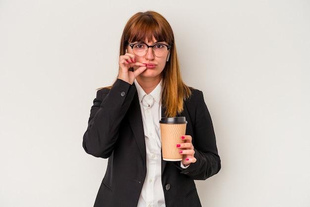 Młoda kaukaski biznes krzywego kobieta trzyma kawę na białym tle z palcami na ustach zachowując tajemnicę.