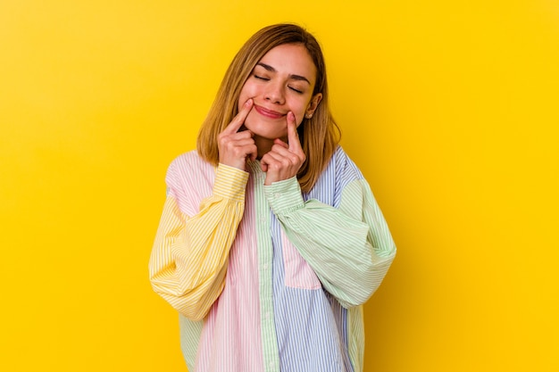 Młoda kaukaski chuda kobieta na żółtym tle wątpiąca między dwiema opcjami.