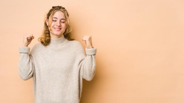 Młoda kaukaski kobieta na białym tle na beżowej przestrzeni świętuje zwycięstwo, pasję i entuzjazm, szczęśliwy wyraz.