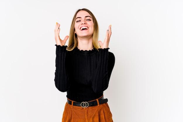 Młoda kaukaski kobieta na białym tle na białym tle głośno się śmieje, trzymając rękę na piersi.