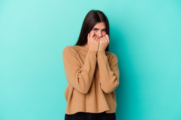 Młoda kaukaski kobieta na białym tle na niebieskiej ścianie gryzie paznokcie, nerwowa i bardzo niespokojna