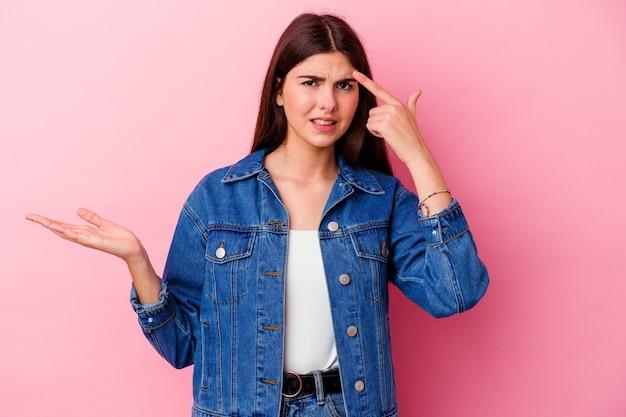 Młoda kaukaski kobieta na białym tle na różowej ścianie pokazując gest rozczarowania palcem wskazującym