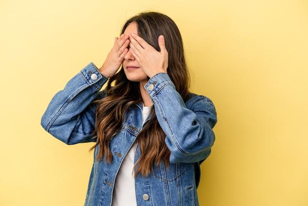 Młoda kaukaski kobieta na białym tle na żółtym tle boi się zasłaniając oczy rękami.