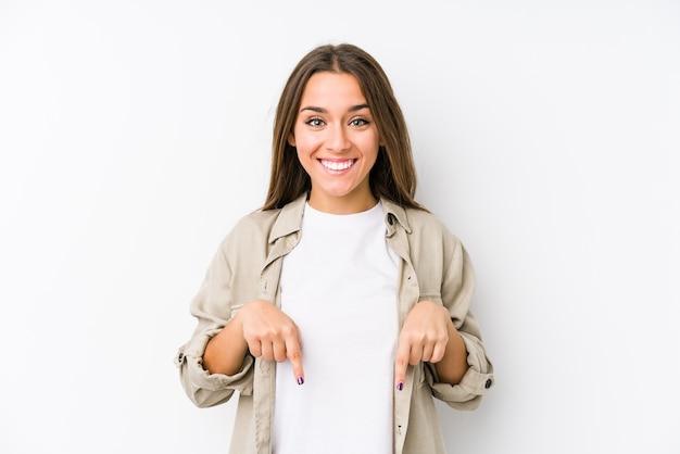 Młoda kaukaski kobieta na białym tle wskazuje palcami w dół, pozytywne uczucie.
