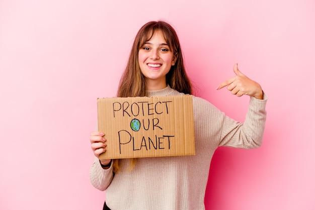 Młoda kaukaski kobieta trzyma afisz chroń naszą planetę, wskazując ręką na przestrzeń kopii koszuli, dumny i pewny siebie