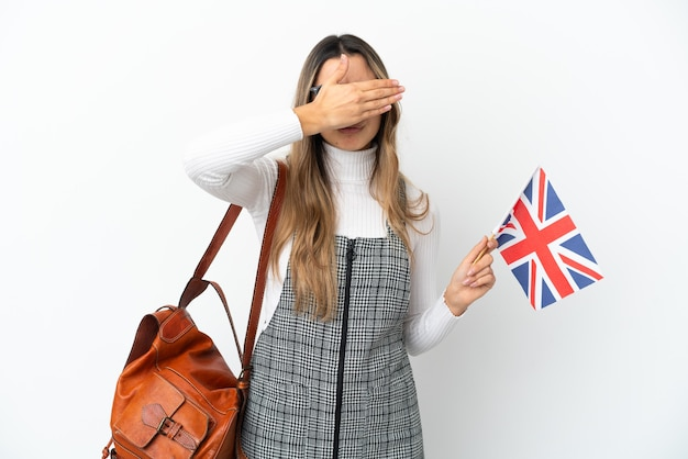 Młoda kaukaski kobieta trzyma flagę wielkiej brytanii na białym tle na białym tle zasłaniając oczy rękami. nie chcę czegoś widzieć
