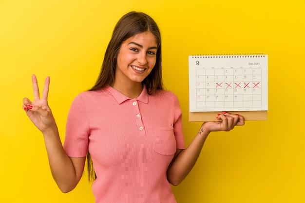 Młoda kaukaski kobieta trzyma kalendarz na białym tle na żółtym tle pokazując numer dwa palcami.