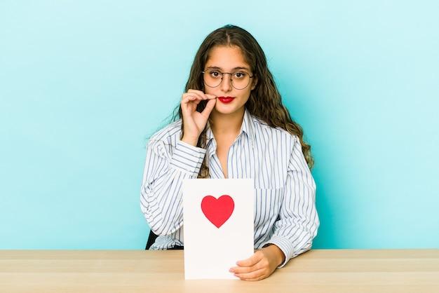 Młoda kaukaski kobieta trzyma kartę walentynki na białym tle z palcami na ustach, zachowując tajemnicę.