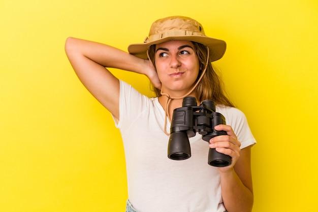 Młoda kaukaski kobieta trzyma lornetkę na białym tle na żółtym tle dotykając tyłu głowy, myśląc i dokonując wyboru.