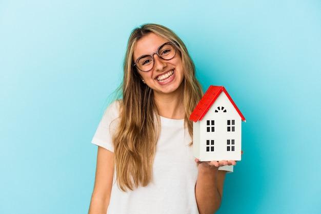 Młoda kaukaski kobieta trzyma model domu szczęśliwy, uśmiechnięty i wesoły.
