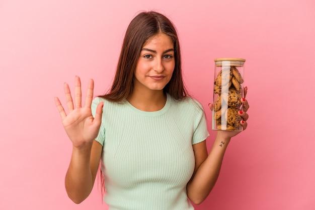 Młoda kaukaski kobieta trzyma słoik ciasteczka na białym tle na różowym tle uśmiechający się wesoły pokazując numer pięć palcami.
