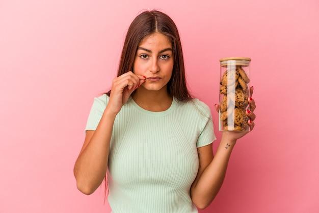 Młoda kaukaski kobieta trzyma słoik ciasteczka na białym tle na różowym tle z palcami na ustach, zachowując tajemnicę.