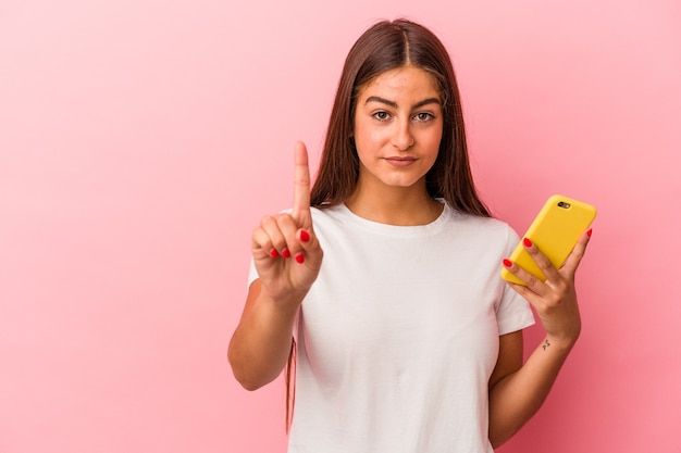 Młoda kaukaski kobieta trzyma telefon komórkowy na białym tle na różowym tle pokazując numer jeden palcem.