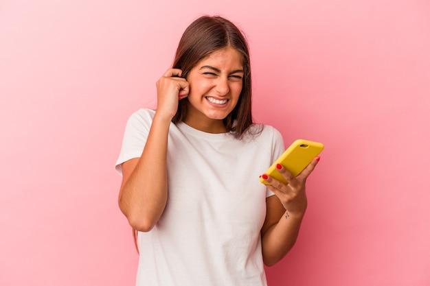 Młoda kaukaski kobieta trzyma telefon komórkowy na białym tle na różowym tle zakrywając uszy rękami.