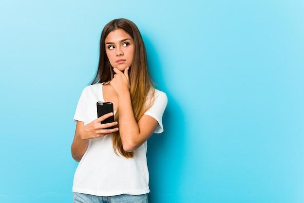 Młoda kaukaski kobieta trzyma telefon patrząc z ukosa z wyrazem wątpliwości i sceptycyzmu.