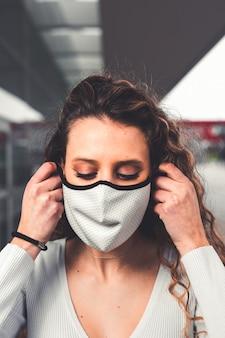 Młoda kaukaski kobieta ubrana w białą maskę na ulicy